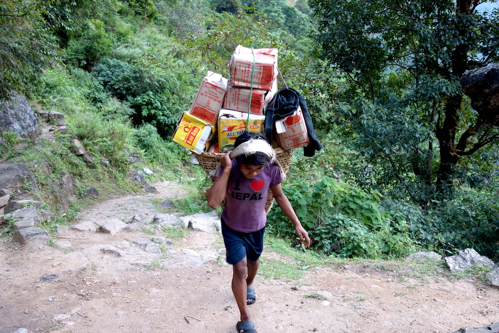 A porter carrying 50kg of weight re-supply a shop in Ghunsa.
