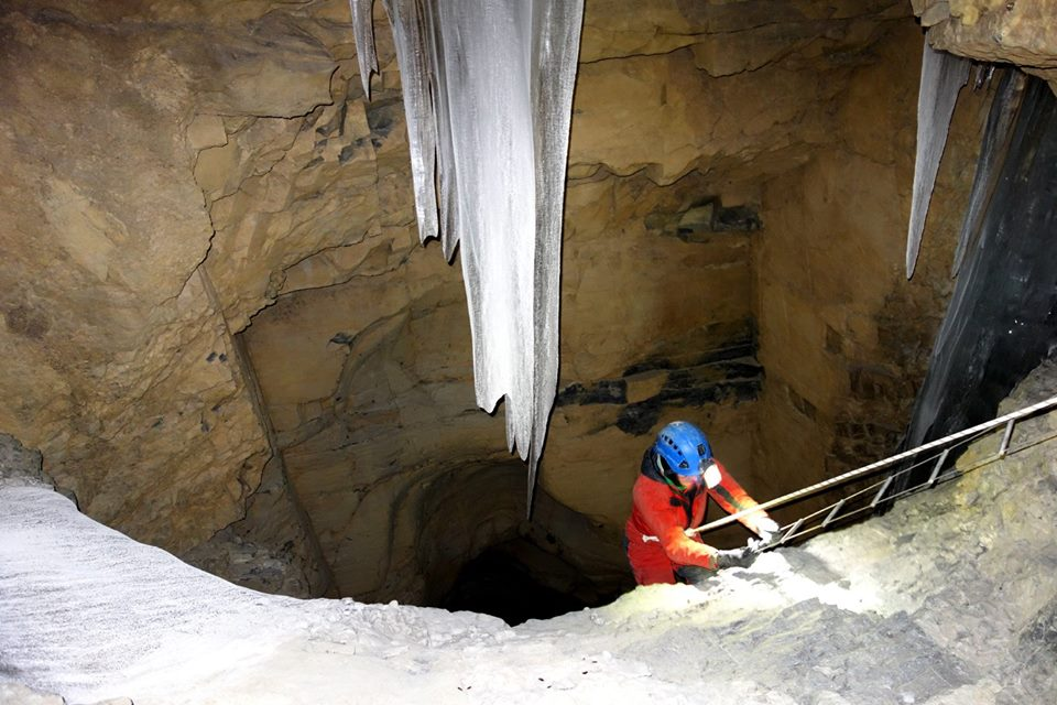 Katie sets up and descends a ladder within the cave.
