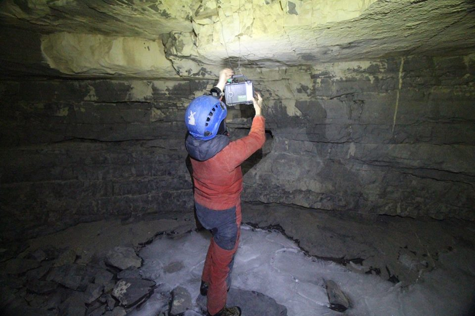 Katie hangs a bat detector in the cave.